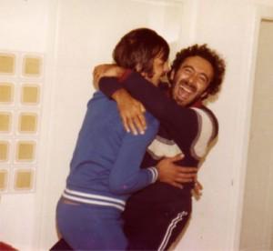 Un momento conviviale durante una serata con amici: Mario ride sonoramente mentre abbraccia un amico con cui accenna un passo di danza